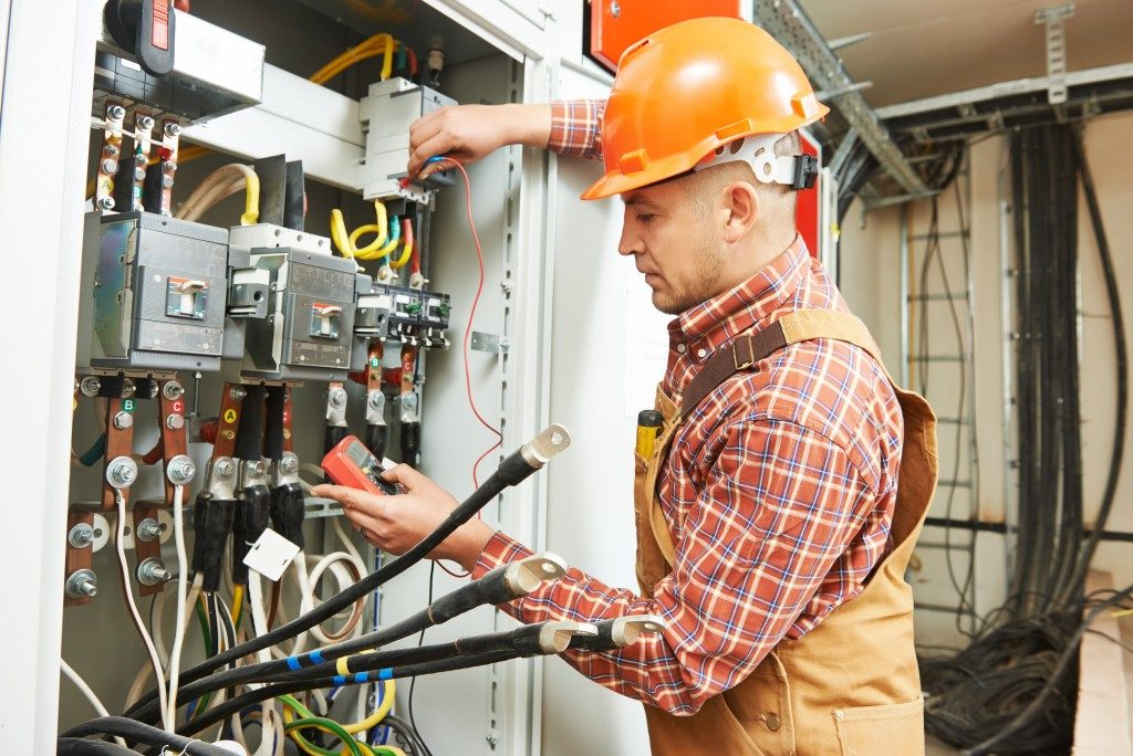 worker in front of fuse switch board