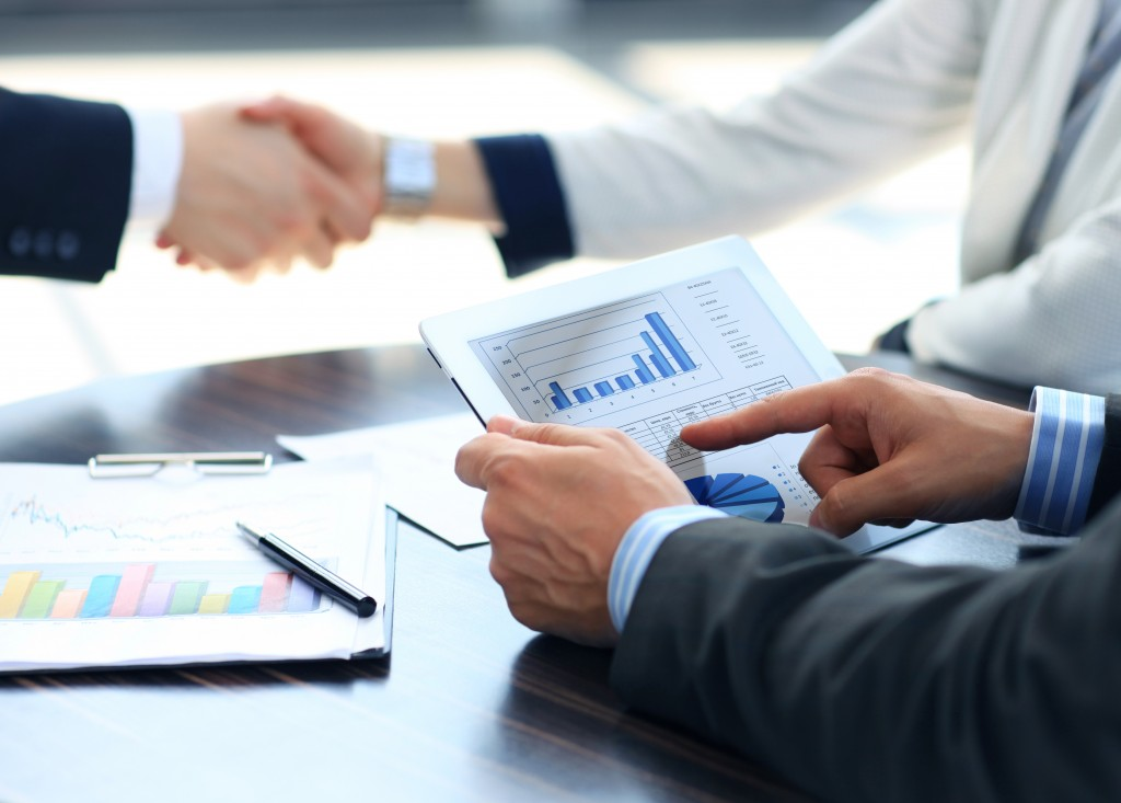 business people shaking hands, man looking at graphs