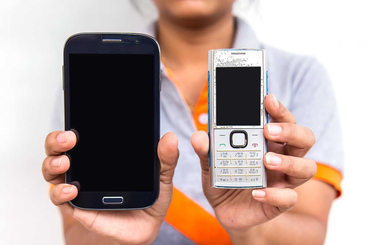 Holding two old mobile phones