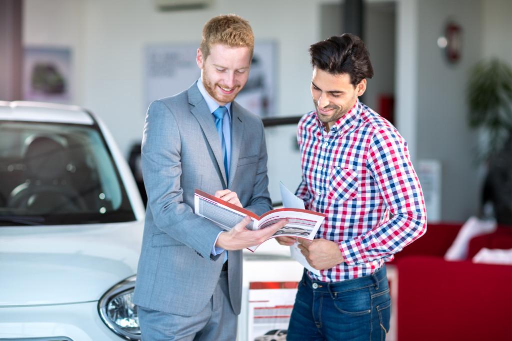 person looking at car catalogue